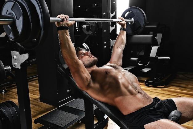 Przystojny młody mężczyzna robi ćwiczenia wyciskanie na ławce w siłowni fitness motywacja sport styl życia zdrowie sportowe ciało