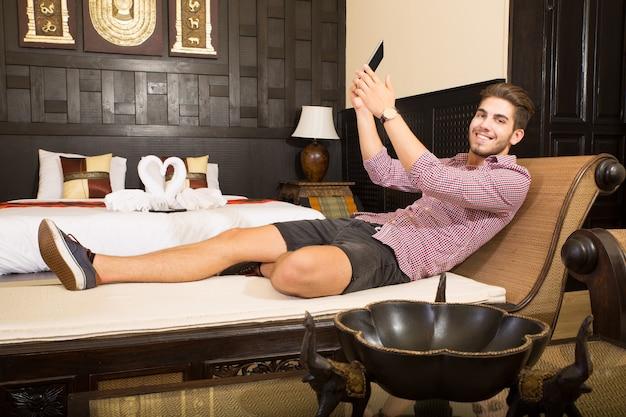 Przystojny młody mężczyzna robi selfie w pokoju hotelowym w stylu azjatyckim.