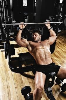 Przystojny młody mężczyzna robi wyciskaniu na ławce w siłowni,