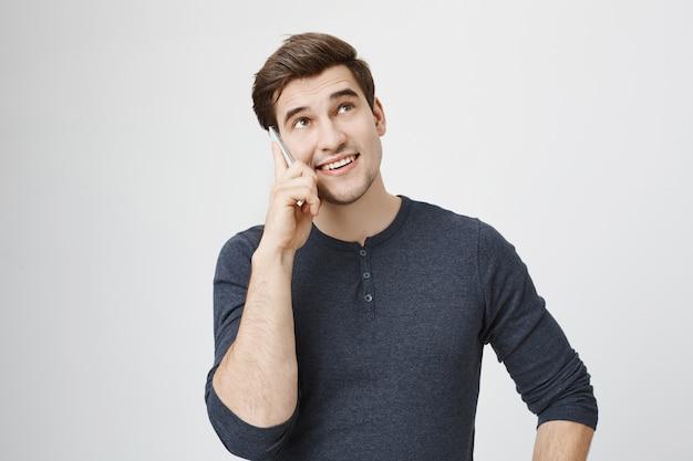 Przystojny młody mężczyzna rozmawia przez telefon i patrząc w górę