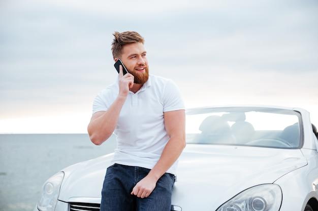 Przystojny młody mężczyzna rozmawia przez telefon komórkowy, opierając się o swój samochód