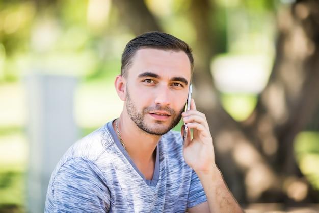 Przystojny młody mężczyzna rozmawia przez telefon siedząc na ławce w parku
