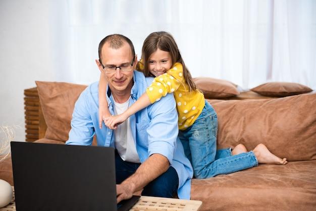 Przystojny młody mężczyzna siedzi na kanapie i pracuje na komputerze przenośnym, pracując zdalnie z domu. samoizolacja społeczna