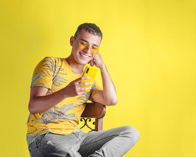 Przystojny młody mężczyzna siedzi na krześle, szczęśliwie sprawdzając swój telefon komórkowy na żółtym tle