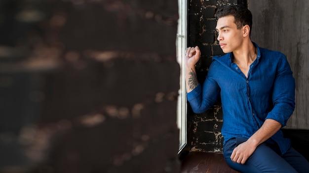 Przystojny młody mężczyzna siedzi na parapecie patrząc przez okno