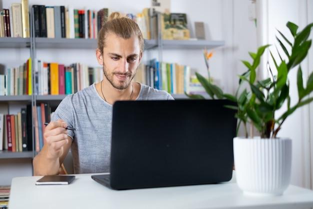 Przystojny młody mężczyzna siedzi przy stole w domu do pracy z laptopem