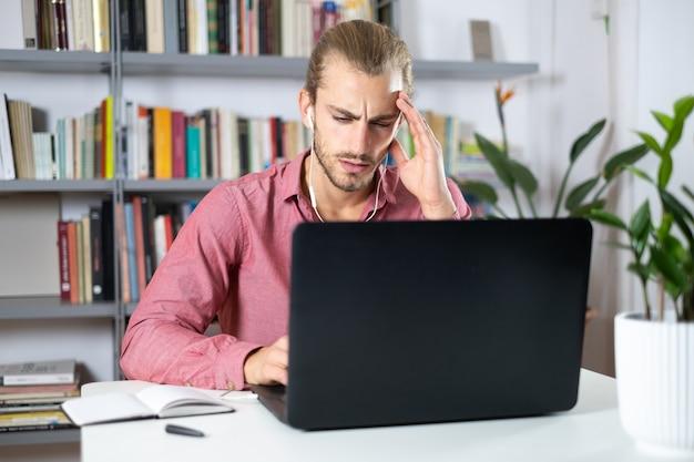 Przystojny młody mężczyzna siedzi przy stole w domu, pracując z laptopem i patrząc zmartwiony