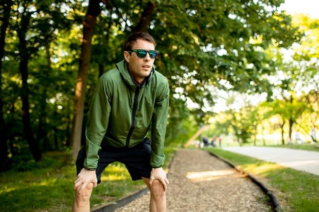 Przystojny młody mężczyzna sportowe po przerwie podczas treningu w słonecznym, zielonym parku