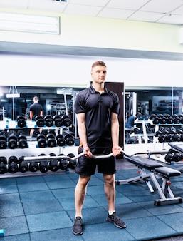Przystojny młody mężczyzna sprawny w sportowej podnoszenia sztangi i pracy na jego bicepsach w siłowni
