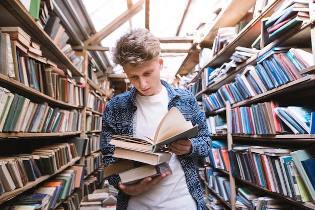 Przystojny młody mężczyzna stoi w starej bibliotece publicznej z książkami w ręku i czyta.