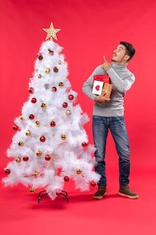 Przystojny młody mężczyzna stojący w pobliżu zdobione białe drzewo nowego roku