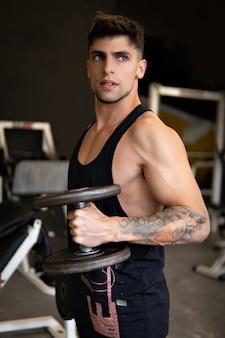 Przystojny młody mężczyzna trenuje bicepsy z hantlami