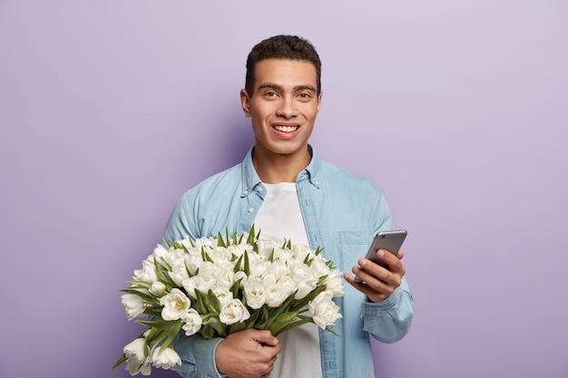 Przystojny młody mężczyzna trzyma bukiet białych tulipanów
