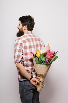 Przystojny młody mężczyzna trzyma bukiet kwiatów za plecami i stojąc przed białą ścianą