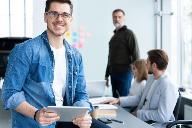 Przystojny młody mężczyzna trzyma cyfrowy tablet i uśmiecha się w biurze