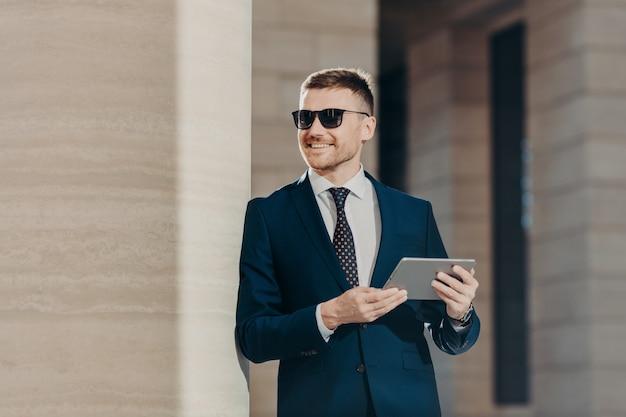 Przystojny młody mężczyzna trzyma cyfrowy tablet, podłączony do bezprzewodowego internetu