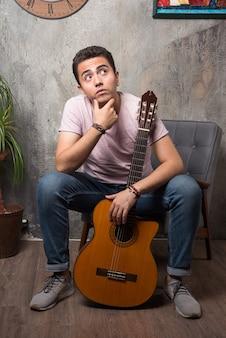 Przystojny młody mężczyzna trzyma gitarę i myśli na krześle.