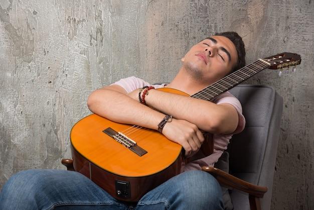 Przystojny młody mężczyzna trzyma gitarę i śpi na krześle.