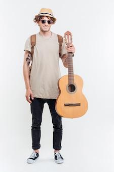 Przystojny młody mężczyzna trzyma na gitarze na białym tle na białym tle okulary przeciwsłoneczne