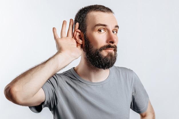 Przystojny młody mężczyzna trzyma rękę przy uchu, chce lepiej słyszeć na białej ścianie