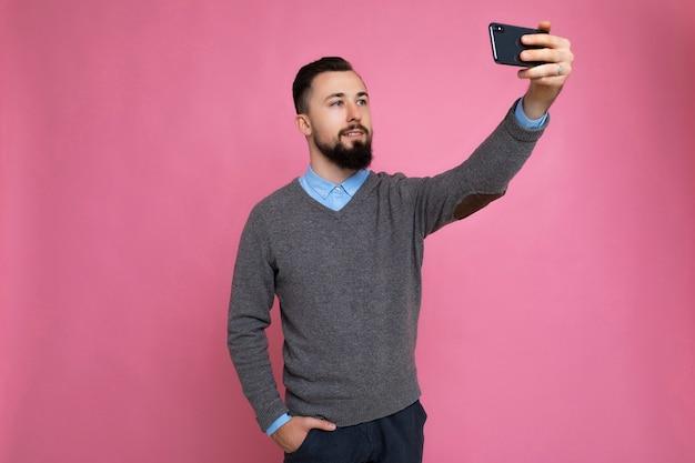 Przystojny młody mężczyzna ubrany dorywczo stylowe ubrania stojący na białym tle nad ścianą w tle, trzymający smartfona, biorąc selfie zdjęcie, patrząc na ekran telefonu komórkowego