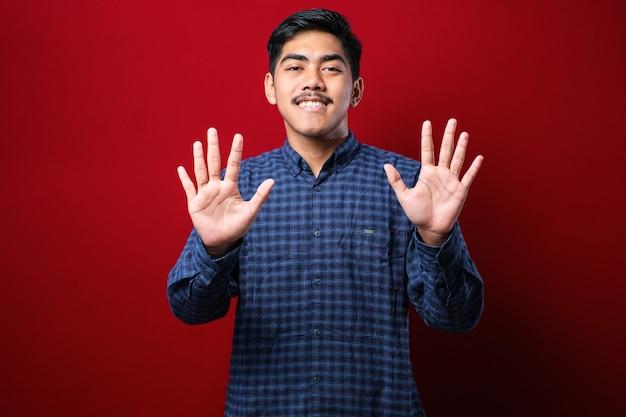 Przystojny młody mężczyzna ubrany na co dzień pokazujący i wskazujący w górę palcami numer dziesięć, uśmiechający się pewnie i szczęśliwy na czerwonym tle