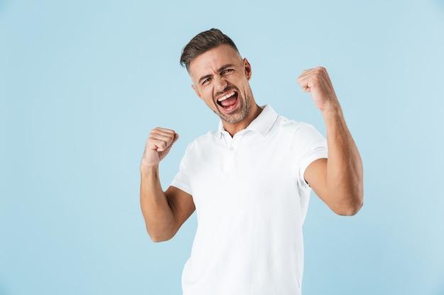 Przystojny młody mężczyzna ubrany w białą koszulkę stojąc na niebiesko, świętuje sukces