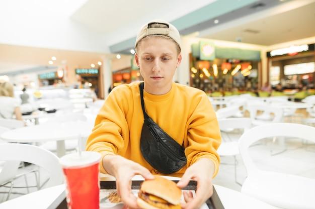 Przystojny młody mężczyzna ubrany w czapkę i żółte ubrania siedzi w recepcji i jedzenie fast food