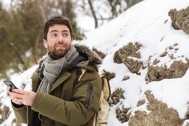 Przystojny młody mężczyzna ubrany w kurtkę zimową za pomocą telefonu komórkowego podczas spaceru na świeżym powietrzu, słuchając muzyki przez słuchawki