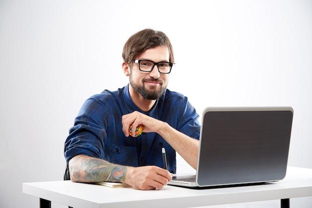 Przystojny młody mężczyzna ubrany w niebieską koszulę i okulary siedzi z laptopem i pracy, koncepcja freelance, portret.
