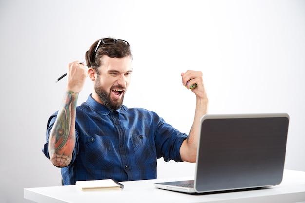 Przystojny młody mężczyzna ubrany w niebieską koszulę siedzi z laptopem i pracy, koncepcja freelance, portret, szczęśliwy zwycięzca, sukces.
