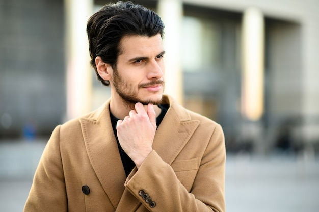 Przystojny młody mężczyzna uśmiechający się na zewnątrz w swobodnych eleganckich ubraniach
