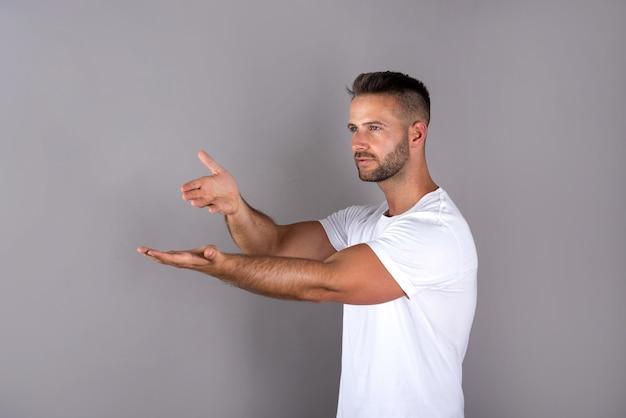 Przystojny młody mężczyzna w białej koszulce pokazuje coś z dłońmi na szaro