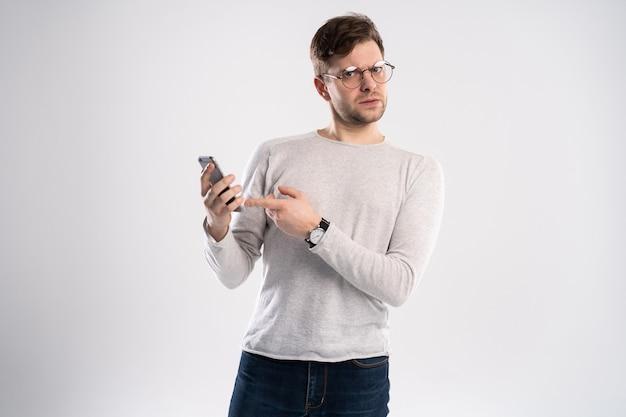 Przystojny młody mężczyzna w białej koszulce, trzymając smartfon, wyglądający na przestraszonego i zdezorientowanego, czytając wiadomość tekstową lub e-mail