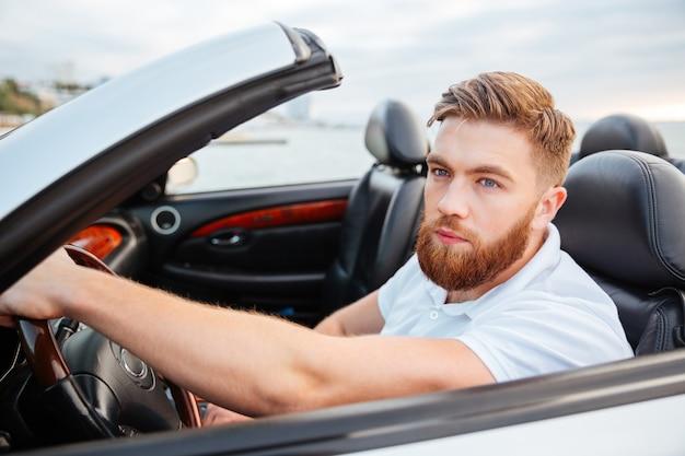 Przystojny młody mężczyzna w białej koszuli jazdy swoim nowym samochodem