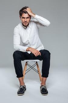 Przystojny młody mężczyzna w białej koszuli pozuje siedząc na krześle nad szarą ścianą