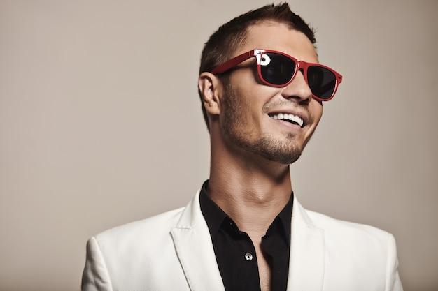 Przystojny młody mężczyzna w białym garniturze z modnymi okularami przeciwsłonecznymi