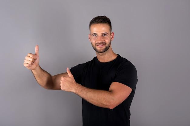 Przystojny młody mężczyzna w czarnej koszulce pokazuje kciuki do góry na szaro