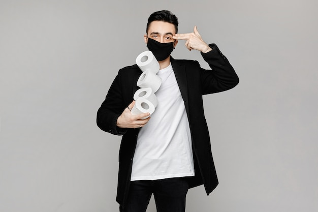 Przystojny młody mężczyzna w czarnej masce ochronnej trzyma rolki papieru toaletowego i pokazuje gest strzelać do mnie. młodzi mężczyźni w maskę ochronną pozowanie z papieru toaletowego