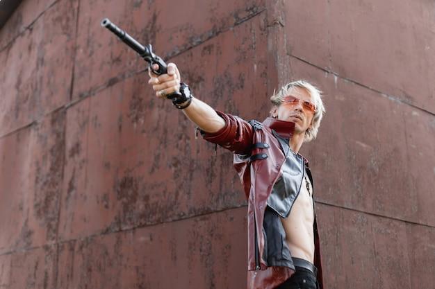 Przystojny młody mężczyzna w czerwonych modnych okularach w modnej skórzanej kurtce z bronią w ręku w pobliżu starego zardzewiałego budynku na zewnątrz