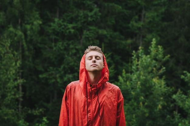 Przystojny młody mężczyzna w czerwonym płaszczu stoi na zewnątrz w deszczu z zamkniętymi oczami i ciesząc się deszczem.
