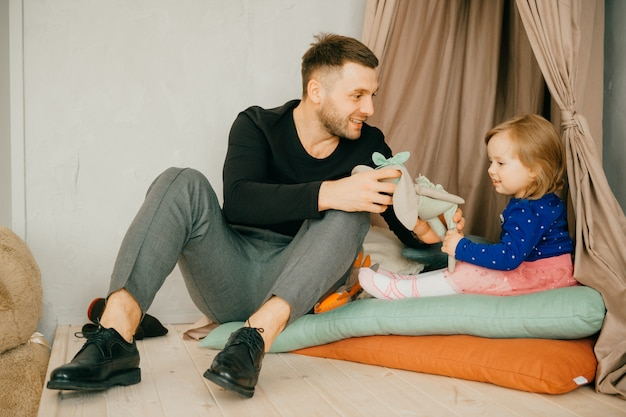 Przystojny młody mężczyzna w domu ze swoją słodką małą dziewczynką.