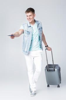 Przystojny młody mężczyzna w dżinsowej kamizelce z walizką daje paszport