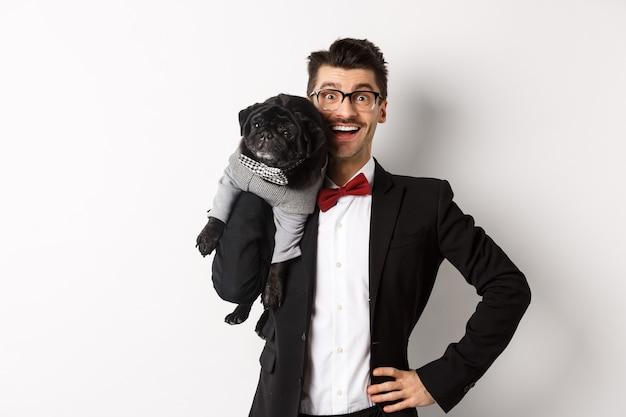 Przystojny młody mężczyzna w garniturze i okularach, trzymając na ramieniu ładny czarny mops pies, uśmiechając się zadowolony do kamery, ubrany w stroje imprezowe, białe tło.