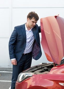 Przystojny młody mężczyzna w garniturze, patrząc pod maską zepsutego samochodu