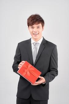 Przystojny młody mężczyzna w garniturze pozuje na białym tle z czerwonym pudełkiem w ręce, patrząc na kamery i uśmiechając się.