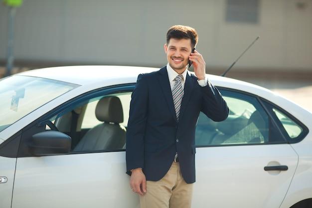 Przystojny młody mężczyzna w garniturze w pobliżu samochodu rozmawia przez telefon