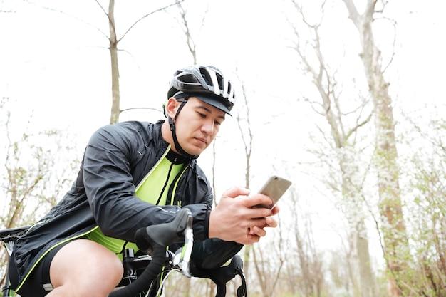 Przystojny młody mężczyzna w kasku rowerowym z rowerem za pomocą smartfona w parku