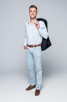 Przystojny młody mężczyzna w koszuli i dżinsach trzyma kurtkę na ramieniu na białym tle na jasnoszarej ścianie