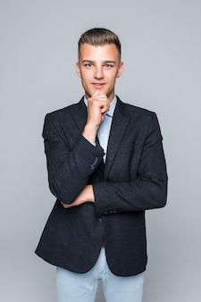 Przystojny młody mężczyzna w koszuli i dżinsach trzyma rękę pod brodą na białym tle